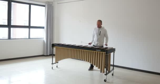 jóképű férfi játszik marimba szóló zenét, négy bottal. Gyönyörű fából készült hangszer. Ez a klasszikus hangszer mindenféle zenét tud játszani, és nagyon népszerű a gyerekek körében.