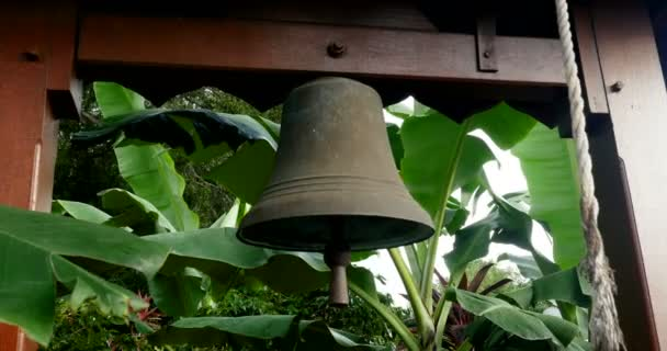 Old outdoor vintage copper and bronze bell with wood frame, green leaves and organic background. fresh beautiful nature in the garden of church with natural plants