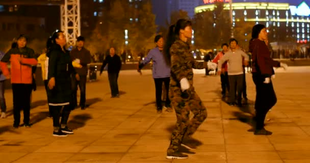 Chinese old people synchronized dancing at night outdoors for chinese new year on a famous city square - the signs in chinese behind : KTV - Dalian, China - February 2019