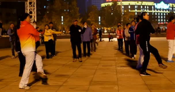 old people dancing at night outdoors on a famous city square - the signs in chinese behind : noodle restaurant, bbq restaurant, and supermarket