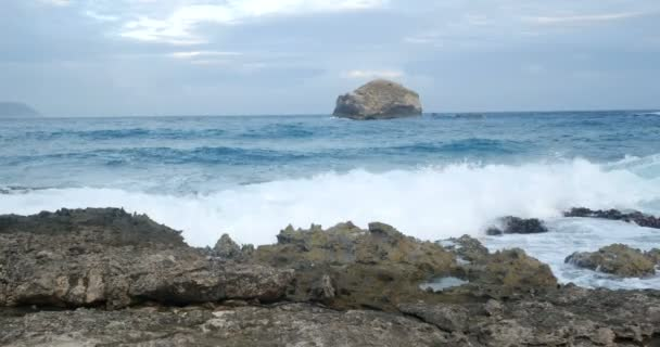 hullámok zuhannak a sziklákra, karibi türkiz óceán drámai felhős égbolttal. nyaralás turizmus és nyaralás az egzotikus tél alatt a színes táj