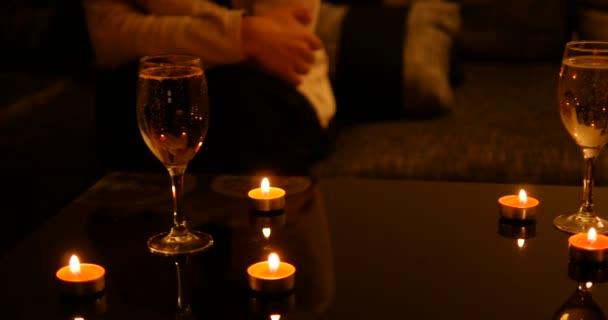 Frauen warten nervös mit Sektgläsern und roten Kerzen auf dem glänzend gedeckten Tisch. Fokus auf linkes Weinglas