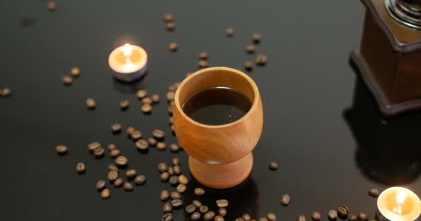 Top view of a traditional Finnish wood mug full of coffee steaming with candles, warm cosy red Christmas candles burning with fresh roasted coffee beans on a black glossy table