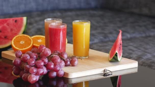 Profesionální barevné 4k záběr čerstvé šťávy. Zdravý životní styl koncept s vitamíny a čerstvým ovocem na dřevěném talíři a černém lesklém stole.