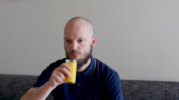 Jóképű szakállas férfi Narancslevet iszik és gondolkodik.