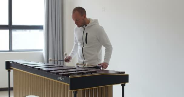 A férfi négy bottal marimbázik. A marimba ütőhangszeres fából készült hangszer gyönyörű hangzással, eredetileg Guatemalából származik, Dél-Amerikából.,