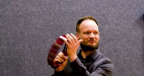 Atraktivní muž hispster hraje tamburínu při pohledu do kamery, profesionální hudebník