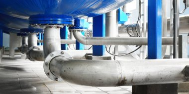 Large industrial water treatment and boiler room. Bottom of large pressure vessels, flanges