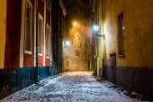 Photo Snow-covered empty street at night. Old Town of Tallinn, Estonia