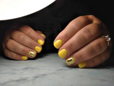 Clean manicure on thick fingers with yellow gel polish and gold