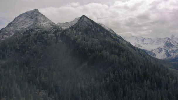Hladký dron filmového záběru zasněžené horské kopce, letecký pohled zasněžené vrcholky hor.