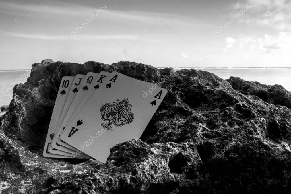 royal flush spade poker cards on beach, gamble theme