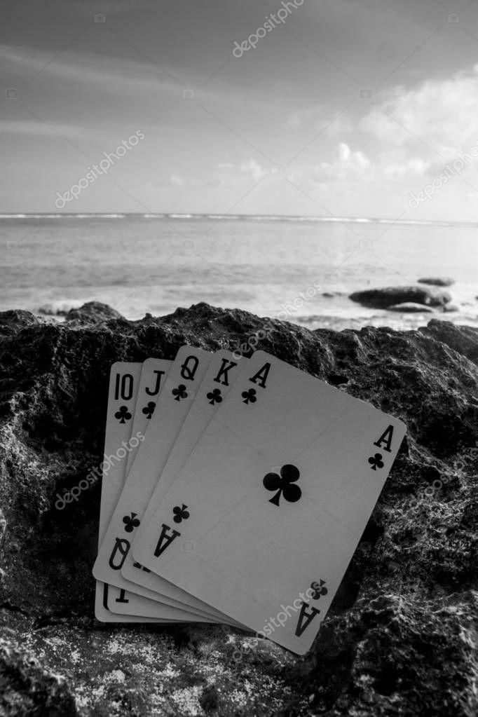club royal flush poker cards on beach, gamble beach theme