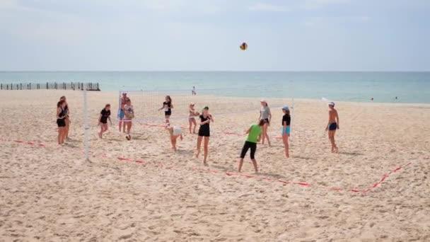 Skupina mladých lidí hrající volejbal na pozadí moře.