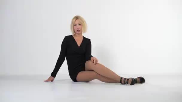 Krásná mladá blondýnka v krátkých černých šatech, které seděly na bílé podlaze zkřížených nohou. Kamera se pohybuje vpředu.