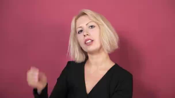 Fiatal gyönyörű szőke lány egy fekete kis ruha egy rózsaszín háttér hullámok haját a kezével. Divat, üzleti, reklám sampon. Közeli.