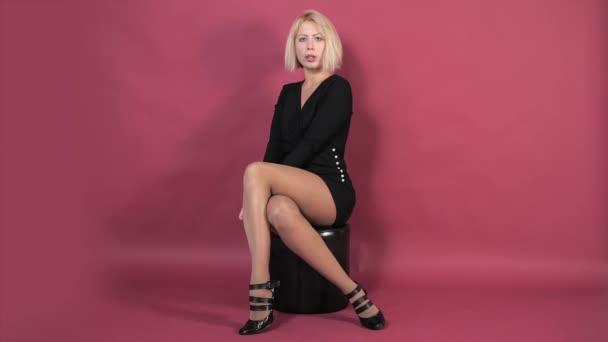 Mladá krásná blondýnka v černých krátkých šatech na růžovém pozadí sedí na nízkém černém koženém křesle a přečítá text. Móda, obchod, reklama.