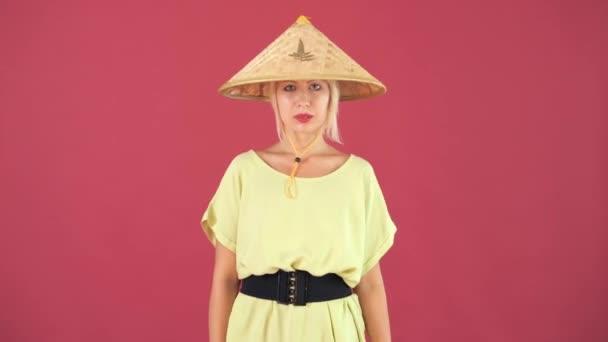 Modenschau eines schönen, sexy, jungen Mädchens. Schöne europäische Mädchen in einem Strohhut und einem gelben Kleid posiert auf einem rosa Hintergrund.