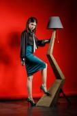 Studioporträt eines jungen Models in lässiger Kleidung auf rotem Hintergrund. junge Frau in schwarzem Hemd und blauem Rock lehnt an stilvoller Holzlampe im Atelierhaus
