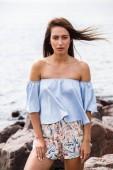 Venkovní snímek krásná mladá hnědovlasá žena na sobě šortky a tričko stojící na skalnaté pláži ve dne