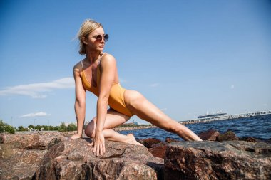 Beauty blond woman wearing sunglasses and swimsuit making fitness on rocky beach at daytime