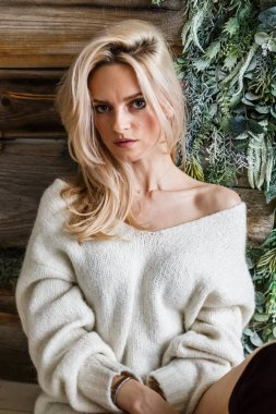 Studio portrait of beauty blond woman wearing white sweater. Female model sitting on wooden floor