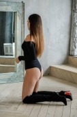 Portrait of beautiful young woman in black clothes. Young model sitting on floor at luxury apartments interior
