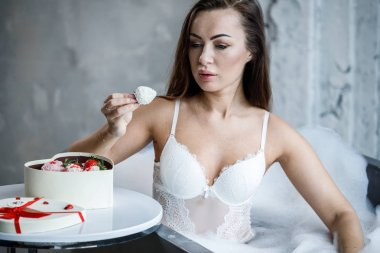 Portrait of beautiful young woman in white lingerie. Model taking bath and eating sweets
