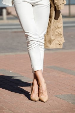 Beauty woman standing outdoors at daytime. Cropped shot of stylish model wearing white pants and heels