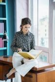 Schöne junge Frau posiert zu Hause Bibliothek Interieur. Porträt der Schönheit Brünette in lässiger Kleidung