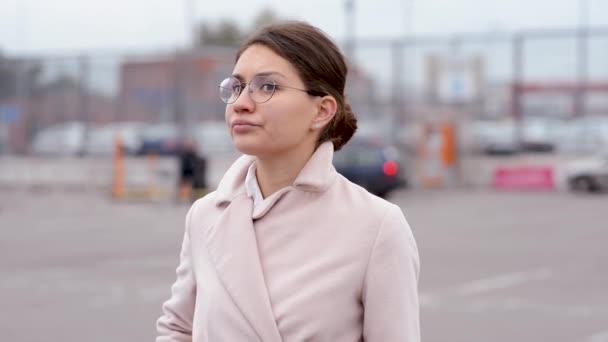 Mladá žena s brýlemi vpluje do oblasti ostrosti, vybere telefon a začne zvonit, hledá něco nebo někoho kolem.