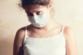Krank aussehendes Mädchen in medizinischer Schutzmaske blickt traurig in die Kamera