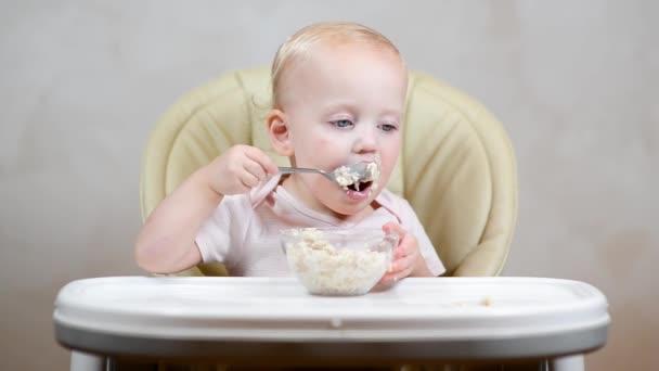 A kislány egyedül tanul meg kanállal enni, és a vonat zabkása, elölnézetből.