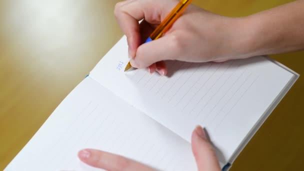 a nő számításokat végez számokkal egy jegyzetfüzetbe írva, és összegezve
