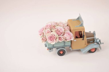 Roses in the back of a toy truck. Free space to place text. The concept of holiday greetings. Light background.