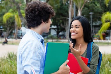 Indian female student talking with caucasian male student outdoor on campus of university