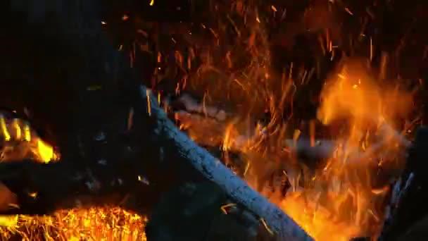 Zuřící oheň v sudu. pálení klád, prken, dřeva, borovic, v sudu. táborák s létajícími jiskry zblízka.