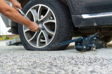 Man changing wheel. tire changer changing flat car tire. Mechanic hands unscrews a flat tire of a car raised on a jack Help on road or Tire help concept.