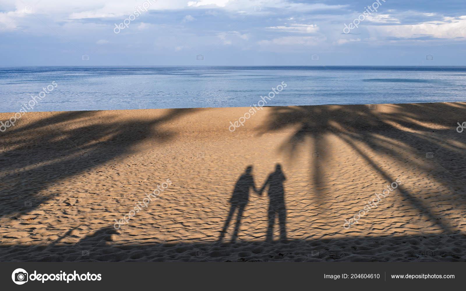 shadow man woman standing holding hands sand beach love concept