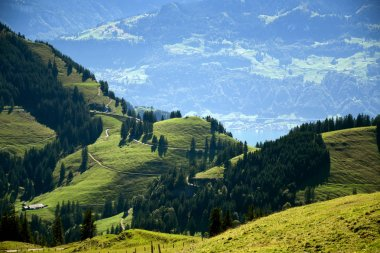 Panoramic landscape view of meadows and mountain ranges with valleys from top of Rigi Kulm, Mount Rigi in Switzerland