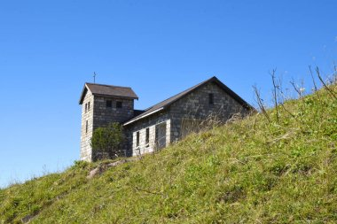 mall brick made church with green grass and blue sky at top of Rigi Kulm, Mount Rigi in Switzerland