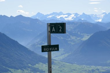 Sign plate with panoramic landscape view of meadows and mountain ranges with snowy mountain peaks from top of Rigi Kulm, Mount Rigi in Switzerland