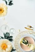 Současné prostírání stolu s pivoňkovými květinami a zlatými příbory na bílém stole. Moderní trendy byt ležel, horní pohled na stůl zdobené žluté a zelené. Letniční projektování, kopírovací prostor.