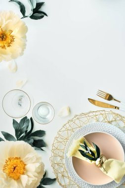 Contemporary table setting with peony flowers and golden utensils on white table. Modern trendy flat lay, top view on table decorated in yellow and green. Pentecost pfingstenrosen design, copy-space. stock vector