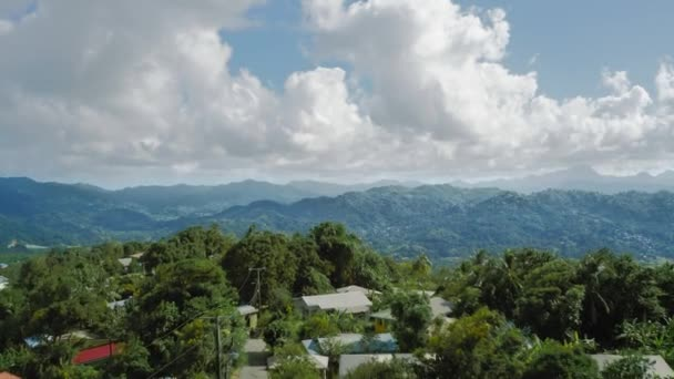 Drone camera moves over the settlement to the cliff, wooded mountains and clouds on the horizon (Saint Lucia)