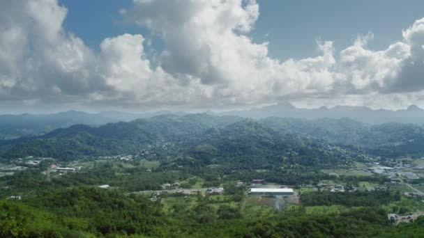 Aerial footage over a settlement in the mountains with a dense forest on the coast of the sea (Saint Lucia)