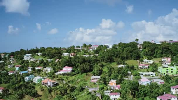 Aerial video shooting of houses with multi-colored roofs and thick trees, blue sky and clouds on the horizon (Saint Lucia)