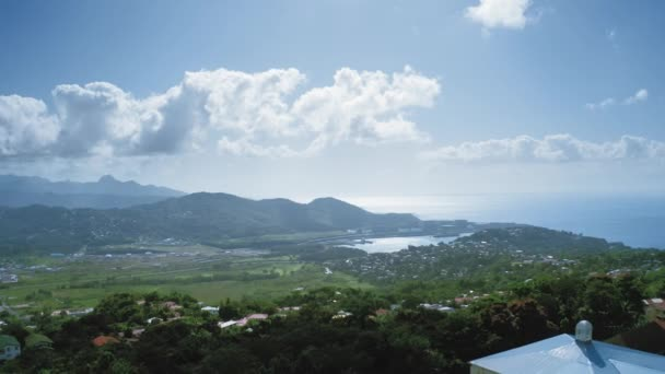 Aerial shot of a city with a dense forest on the mountainous coast of the bay (Saint Lucia)