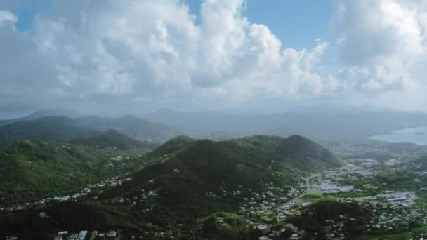 Aerial drone flies over wooded mountains with a settlement and a winding road, near the sea and foggy horizon (Saint Lucia)