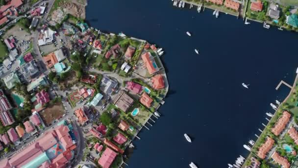 Drone removes a top-down view of the harbor with yachts, roofs of houses, pools, a road with cars and the seashore (Rodney Bay, Saint Lucia)